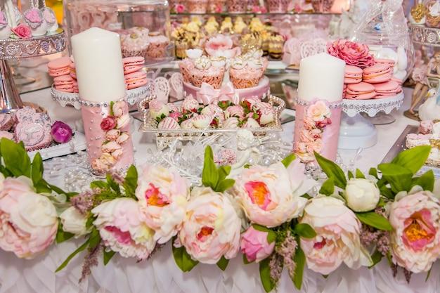 Вкусные десерты на свадебном кэнди-баре в зоне фуршета: декорированные свечи, бутоны роз, ленты, макаруны, клубника в белом шоколаде.