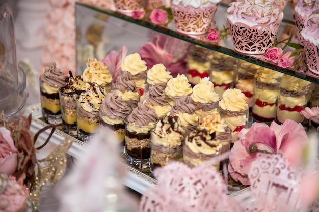 ビュッフェエリアのウェディングキャンディーバーでのおいしいデザート:チョコレート、クリーム、ナッツ、スフレ、ホイップクリームを重ねたデザートのグラス