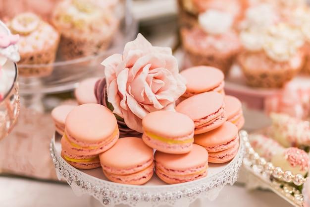 Вкусные десерты в свадебном моноблоке в зоне фуршета: макаруны, украшенные головками роз.