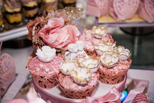 뷔페 공간의 웨딩 캔디 바에서 맛있는 디저트: 천사, 설탕 장미 봉오리, 금색 염료로 장식된 머핀