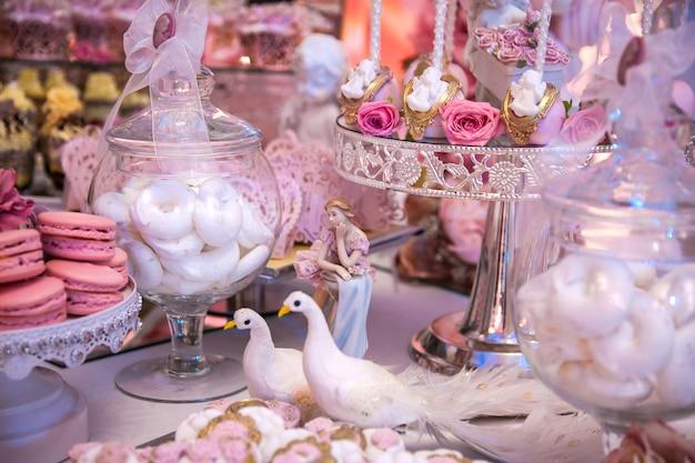 Вкусные десерты в свадебном моноблоке в зоне фуршета: статуэтка, фигурка, торт, зефир, безе.