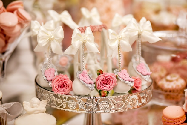 Delicious desserts at the wedding candy bar in the buffet area: cake pops decorated with angels and cameo and fresh rosebuds