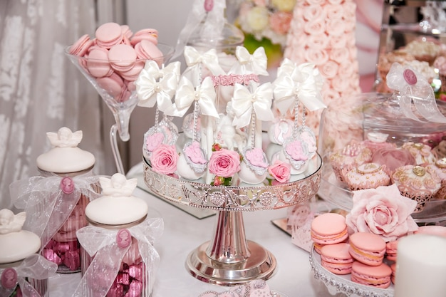 Delicious desserts at the wedding candy bar in the buffet area: cake pops decorated with angels and cameo and fresh rosebuds.