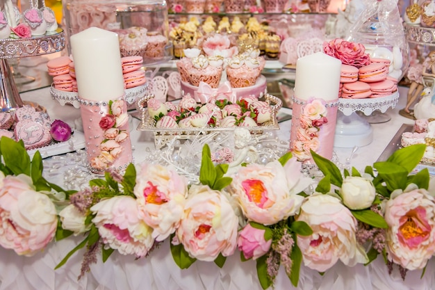Delicious desserts at the wedding candy bar in the buffet area: decorated candles, rosebuds, ribbons, macaroons, strawberries in white chocolate