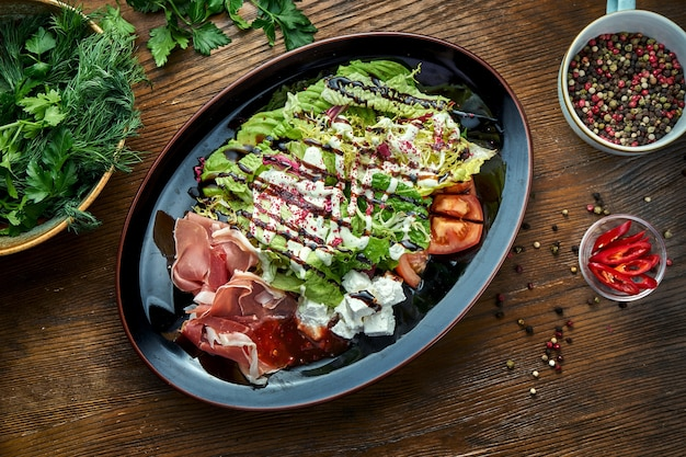 Delicious and dietary salad with jamon, feta cheese, tomatoes, served in a black plate on a wooden table. restaurant food