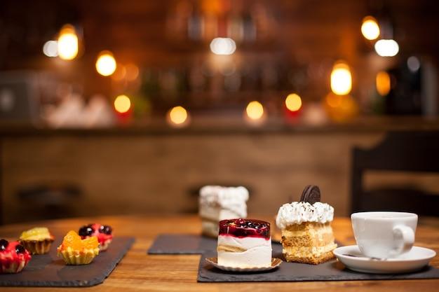 コーヒーショップの木製のテーブルの上においしいコーヒーのカップとおいしい異なるケーキ。一杯のコーヒーとケーキの盛り合わせの写真。美味しいビスケットをのせた美味しいケーキ。
