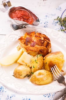 Delicious dinner: baked potatoes with thyme and cutlets