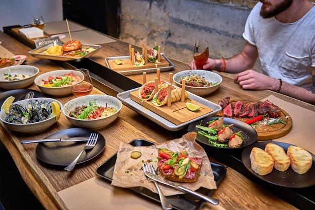 木製のテーブルの上のレストランでおいしい夕食。カフェやパブのメニューでビールと一緒においしい料理。