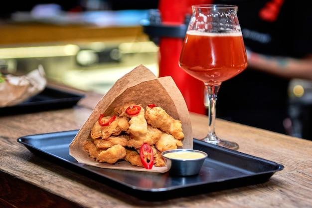 나무 테이블에 레스토랑에서 맛있는 저녁 너 겟. 카페 또는 펍 메뉴 바 카운터에서 맥주와 함께 맛있는 음식.