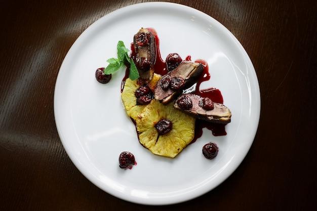 暗い壁の上面図のプレートでのおいしいディナー。パイナップルとイチゴのおいしい豚肉