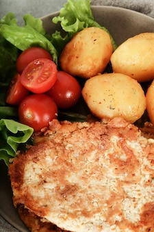 Delicious dinner with steaks, boiled potatoes and salad