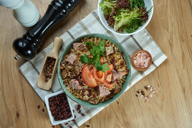 A delicious dish of eastern cuisine - pilaf with pork and tomatoes in a blue bowl on a . top view. food flat lay