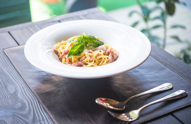 Delicious dish of spaghetti with meat and basil leaf on wooden table