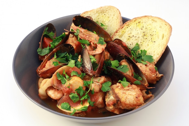 Delicious dish with seafood soup and baked bread