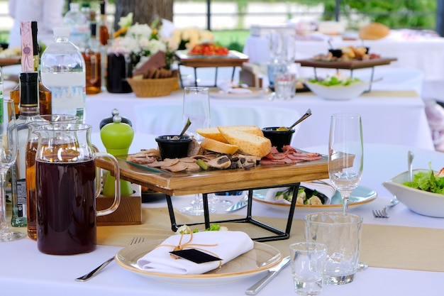Delicious dishes on wooden trays and drinks on a banquet table in a luxury restaurant