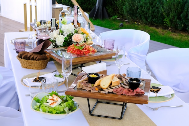 Delicious dishes on wooden trays and drinks on a banquet table in a restaurant.