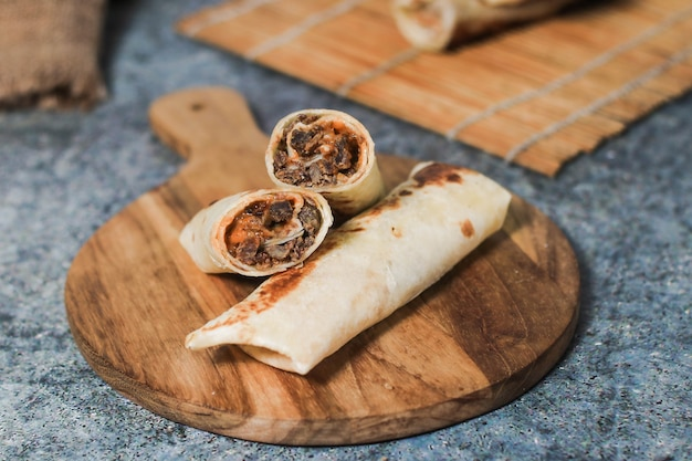 A delicious doner donair kebab wrap with spicy meat lettuce tomato red onion and sauce