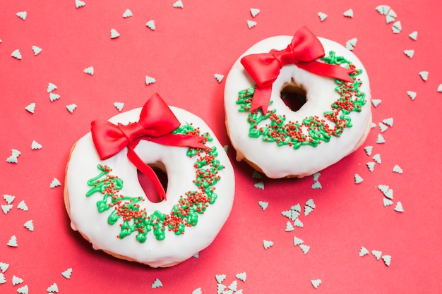Delicious donut decorated for christmas on red backdrop with sprinkles