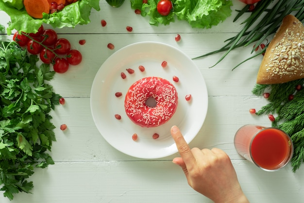 A delicious donut lies on a plate and eats to eat it. problems of proper nutrition and the concept of choosing between wholesome and not wholesome food