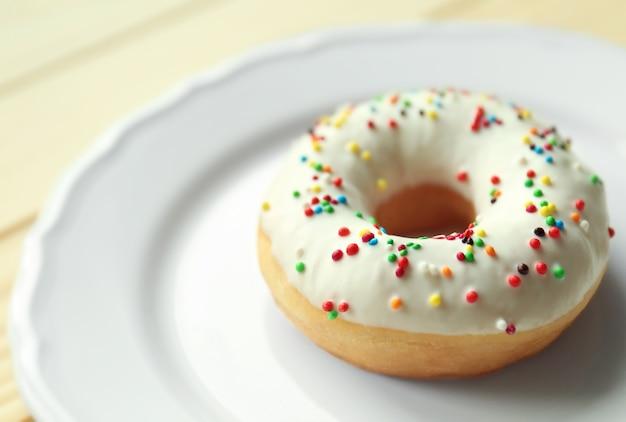 Вкусный пончик на тарелке, крупным планом