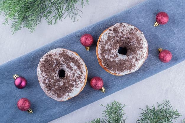 Вкусные пончики и рождественские украшения на сложенной скатерти на белом фоне.