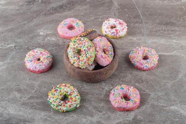Delicious donuts in and around a small bowl on marble surface