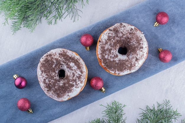 Delicious donuts and christmas decorations on a folded tablecloth on white background.