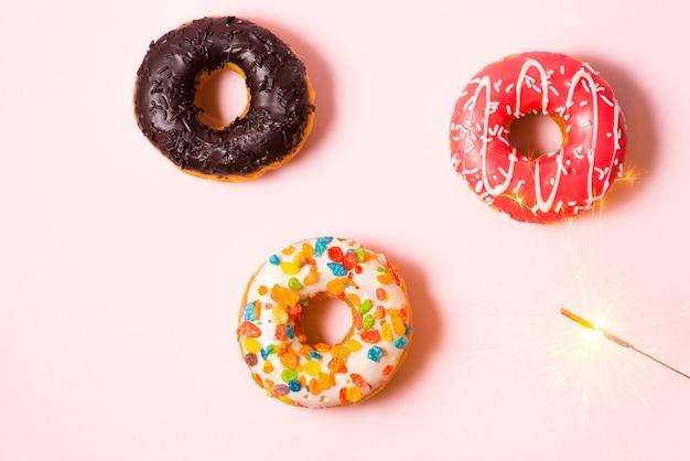 파스텔 핑크 배경에 생일을 위한 맛있는 도넛.
