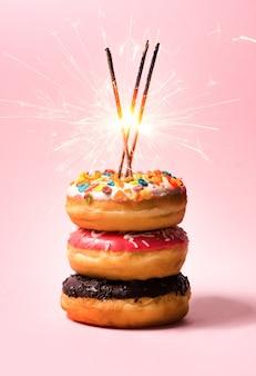 파스텔 핑크 배경에 생일을 위한 맛있는 도넛