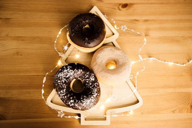クリスマスツリーの形をしたプレートに花輪を添えたチョコレートのアイシングとおいしいドーナツ