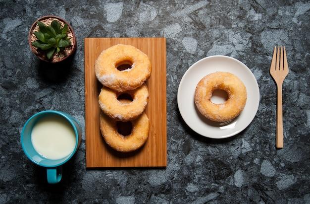 장식 및 검은 대리석 테이블에 접시에 우유 한잔 맛있는 도넛.