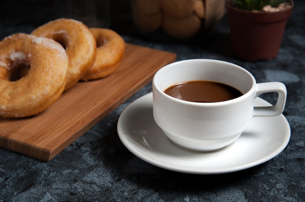 Delicious donuts with icing and cup of coffee in plate on black marble table.