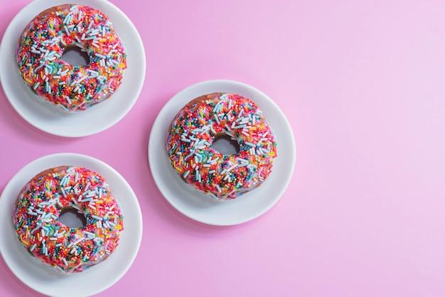 Вкусные пончики с разноцветной посыпкой на розовом фоне.