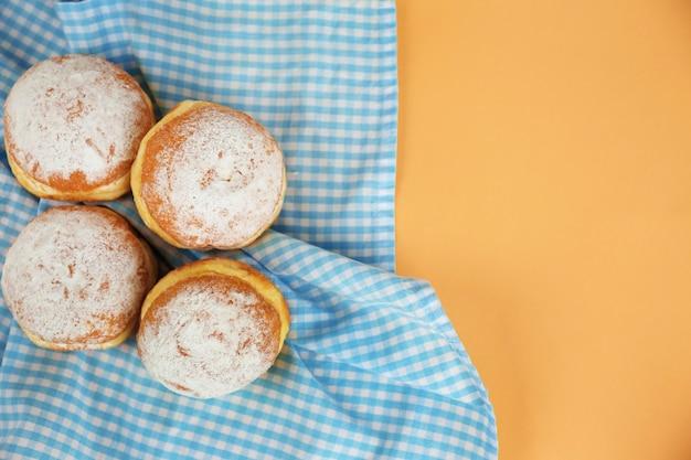 ナプキンの上面図に粉砂糖が入ったおいしいドーナツ