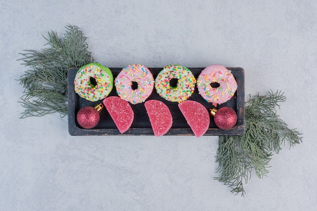 Вкусные пончики с разбрызгивателями и мармеладом на черной тарелке.