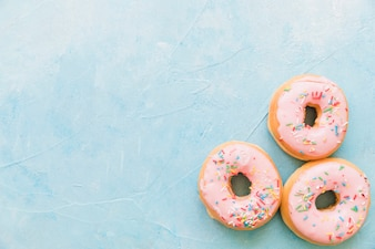 Delicious donuts with sprinkles on blue backdrop
