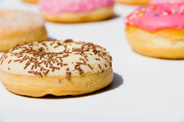 Delicious donuts with sprinkles on white backdrop