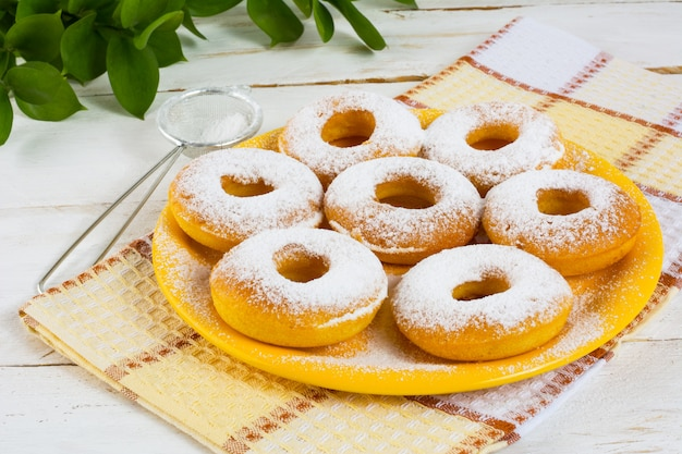 Delicious donuts on yellow plate