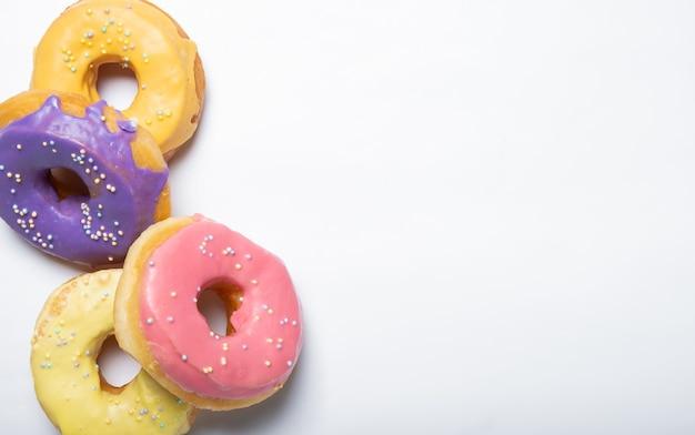 Вкусные пончики на белой поверхности