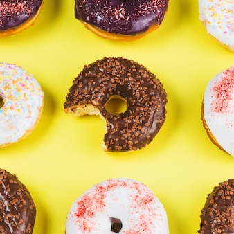 Delicious doughnuts with icing and missing bite on yellow background