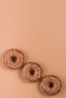 Delicious doughnuts with icing on brown background