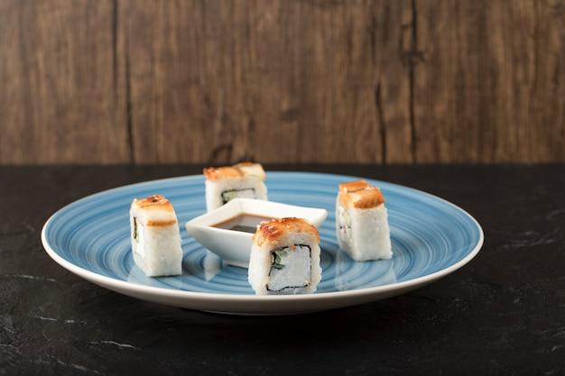 파란색 접시에 맛있는 용 스시 롤과 간장