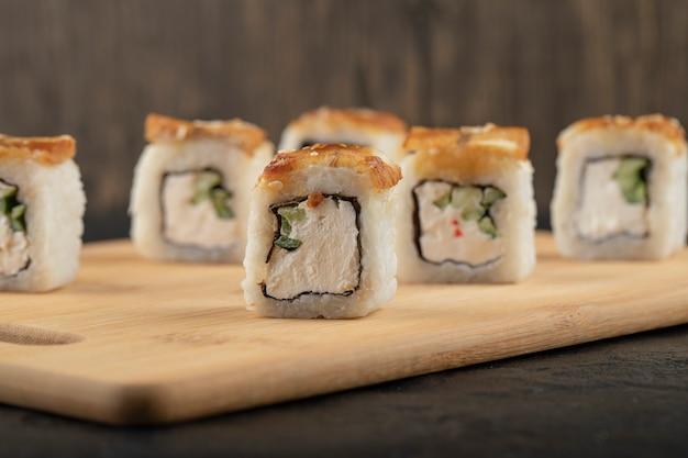 Deliziosi involtini di sushi di drago con anguilla su tagliere di legno