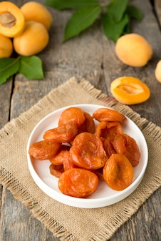 Delicious dried apricots on a wooden table.