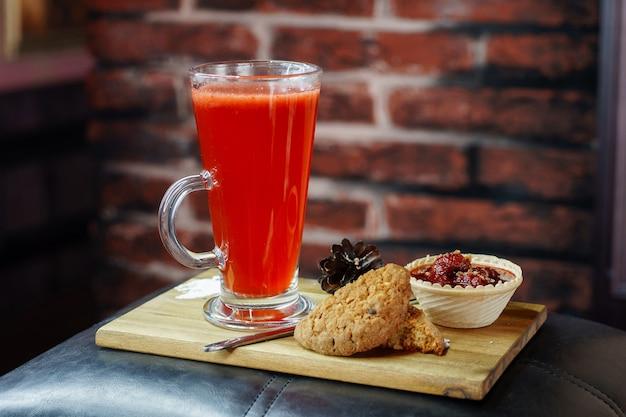 Вкусный напиток в кружке с печеньем и клубникой в корзине на деревянной доске