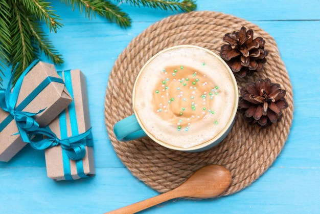 Delicious drink with foam and the addition of sweet powder with cones and fir needles.