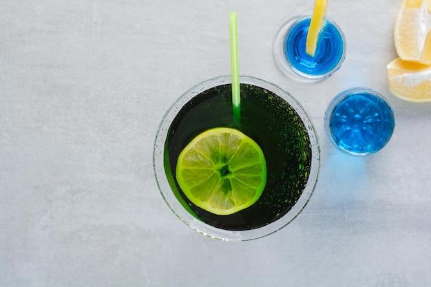Вкусный напиток с соломой и лимоном на мраморном фоне. фото высокого качества