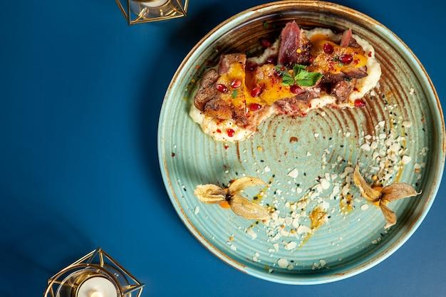 磁器にマッシュポテトとフルーツを添えたおいしい鴨胸肉、美食