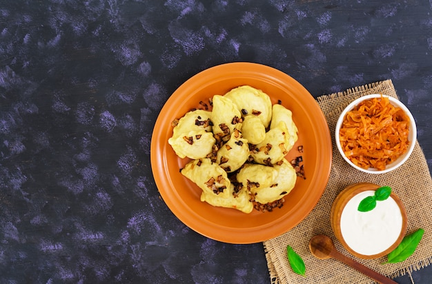 Delicious dumplings with cabbage and sour cream on dark