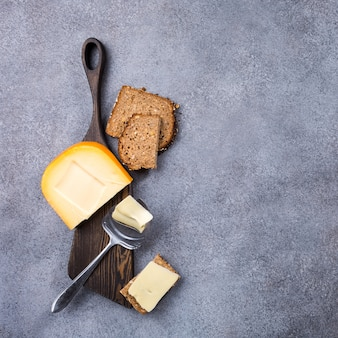Delicious dutch gouda cheese with cheese slices, multigrain bread and special knife on old wooden board.